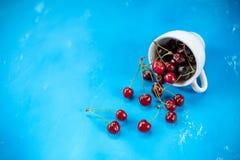 Witte kop met rijpe bessen van rode zoete kers en verscheidene bessen voor de kop Samenstelling op een blauw stock foto