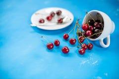 Witte kop met rijpe bessen van rode zoete kers en verscheidene bessen voor de kop Samenstelling op een blauw stock afbeeldingen