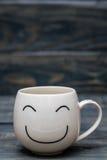 Witte Kop met Smiley Face op Blauwe Houten Lijst stock fotografie