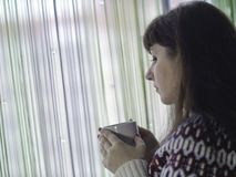 Witte kop met thee in de handen van een jonge vrouw die zich door het venster bevinden royalty-vrije stock foto's