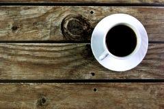 Witte kop met zwarte koffie op bruine houten achtergrond Mening van hierboven stock fotografie
