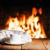 Witte kop thee of koffie en wollen sjaal dichtbij open haard stock afbeeldingen