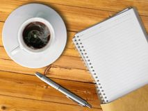 Witte kop van hete koffie en blanco paginanotaboek Stock Foto