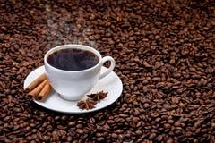 Witte kop van hete koffie op koffiebonen Stock Afbeeldingen