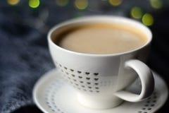 Witte kop van koffie met een hartpatroon en lichten op de achtergrond royalty-vrije stock foto's