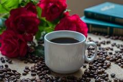 Witte kop van koffie, met koffiebonen op boekenachtergrond Royalty-vrije Stock Foto