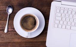 Witte kop van koffie met lepel en notitieboekje op natuurlijke houten lijst royalty-vrije stock afbeeldingen
