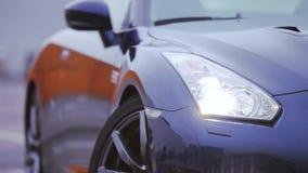 Witte koplampen van donkerblauwe nieuwe autotribune op parkeren Presentatie van auto Koude schaduwen stock videobeelden
