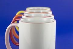 Witte koppen met gekleurde pennen op blauwe achtergrond Stock Foto