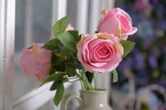 Witte kruik met roze rozen royalty-vrije stock afbeeldingen