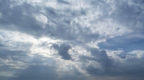 Witte krullende wolken in een blauwe hemel met donkere wolken De achtergrond van de hemel Royalty-vrije Stock Afbeeldingen