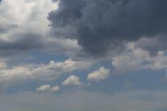 Witte krullende wolken in een blauwe hemel met donkere wolken De achtergrond van de hemel Royalty-vrije Stock Foto