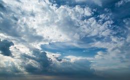 Witte krullende wolken in een blauwe hemel met donkere wolken De achtergrond van de hemel Royalty-vrije Stock Afbeelding