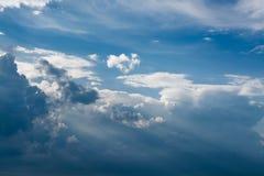 Witte krullende wolken in een blauwe hemel met donkere wolken De achtergrond van de hemel Stock Fotografie
