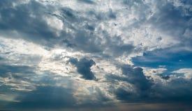 Witte krullende wolken in een blauwe hemel met donkere wolken De achtergrond van de hemel Stock Afbeeldingen