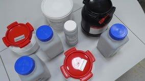 Witte laboratoriumkruiken op een lijst in een laboratorium Voorbereidingen in kruiken stock video