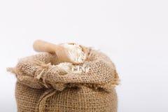 Witte lange rijst in jutezak met houten lepel royalty-vrije stock fotografie