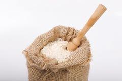 Witte lange rijst in jutezak met houten lepel stock foto