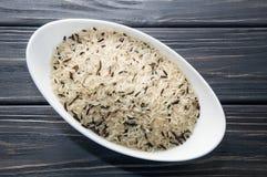 Witte langwerpige die kom met wilde rijst wordt gevuld Donkere houten achtergrond royalty-vrije stock foto's