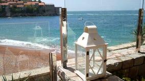 Witte lantaarn op het kuststrand in Montenegro stock video