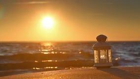 Witte lantaarn op het strand bij zonsondergang stock videobeelden
