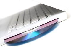Witte laptop met dvdschijf in geïsoleerdei groef. Schuine stand stock foto