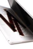 Witte laptop met gekleurde negatieve films op een sleutel royalty-vrije stock afbeelding