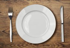 Witte lege dinerplaat die op houten lijst plaatsen royalty-vrije stock foto's