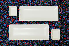 Witte lege platen op het donkere kleurrijke tafelkleed stock fotografie