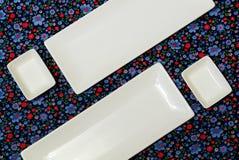 Witte lege platen op het donkere kleurrijke tafelkleed stock foto