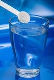 Witte lepel meer dan een glas water Royalty-vrije Stock Fotografie