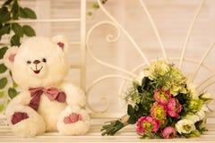 Witte leuke teddybeerzitting op schommeling met bloemen voor ogenblik van liefdeconcept Royalty-vrije Stock Foto's