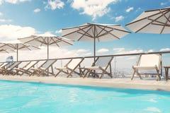 Witte ligstoelen, paraplu's, stad, kant Royalty-vrije Stock Afbeeldingen