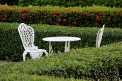 Witte lijst en stoel in tuin Stock Fotografie