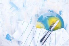 Witte lijst met gekleurd blauw Een witte handdoek met blauwe strepen Een mooie plaat met een vork en een mes Vrije ruimte voor te royalty-vrije stock afbeeldingen