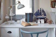 Witte lijst met houten stoelboeken en lamp op moderne werkplaats stock foto