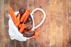 Witte linnenzak met gewassen niet genormaliseerde lelijke groente op houten lijst stock foto