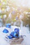 Witte mand met decoratieve Kerstmisballen op de sneeuw en blauwe ballen op Kerstmisboom Stock Afbeelding