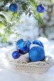 Witte mand met decoratieve Kerstmisballen op de sneeuw en blauwe ballen op Kerstmisboom Stock Afbeeldingen
