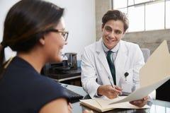 Witte mannelijke arts die dossier tonen aan vrouwelijke patiënt in bureau stock foto