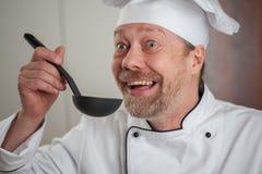 Witte mannelijke Cook in de keuken met een gietlepel Royalty-vrije Stock Foto's