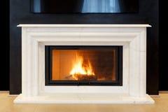 Witte, marmeren open haard en brandende brand Stock Foto's
