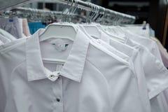 Witte medische robes op hangers Sluit omhoog royalty-vrije stock afbeelding