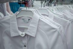 Witte medische robes op hangers Sluit omhoog royalty-vrije stock fotografie