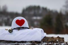Witte militaire helm met groot rood hart Het de winter van ` s royalty-vrije stock fotografie