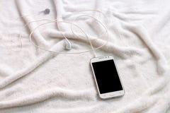 Witte mobiele telefoon met hoofdtelefoons op een handdoek Stock Fotografie