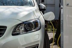 Witte moderne insteekauto die die en zijn batterij belast met groene elektriciteit wordt gestopt royalty-vrije stock foto