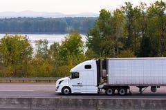 Witte moderne semi vrachtwagen met adelborst op weg langs rivier Colum Royalty-vrije Stock Afbeelding