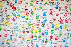 Witte muur met kleurrijke afdrukken van kinderenhanden stock afbeeldingen