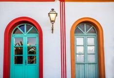 Witte muur met kleurrijke deuren en lantaarn Stock Afbeelding